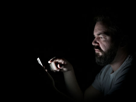 Man using his Mobile Cell Phone at night, lit by phone, isolated on black Background, in profile.