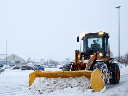 Żółty pług śnieżny do odśnieżania odśnieżania parkingu podczas burzy w Bemidji, Minnesota. Dostępny materiał wideo. Zdjęcie Seryjne