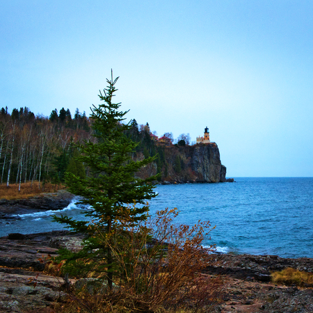 Split Rock Lighthouse on the north shore of Lake Superior near Duluth and Two Harbors, Minnesota. Evergreen tree in foreground.
