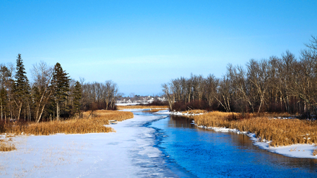 Mississippi River flows north toward Bemidji Minnesota near hiway 2 on a sunny day. This winter scene with snow and ice is a few miles from the source at Lake Itasca