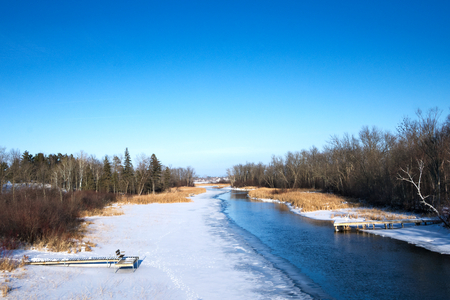Mississippi River flows north toward Bemidji Minnesota near hiway 2 on a sunny day. This winter scene includes boat docks in snow and ice. Stok Fotoğraf