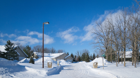 Snow piles along street with houses in Minnesota residential community after winter storms with blue sky and a few clouds.