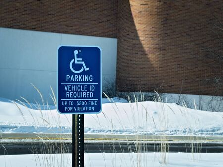 Handicapped parking sign posted in snow covered parking lot in winter.