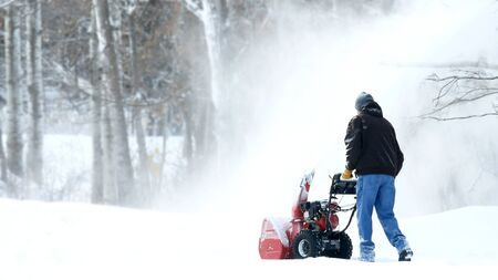Man works with a snow blower to remove newly fallen snow from driveway after storm in Minnesota. Video footage available.