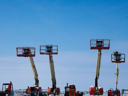 Telescopic Boom Lifts in snowy winter storage area with blue sky.