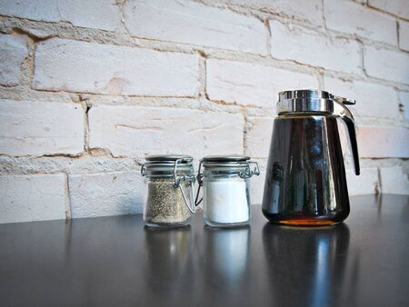Salt and pepper shakers and syrup dispenser with reflection on cafe table next to a painted brick wall.