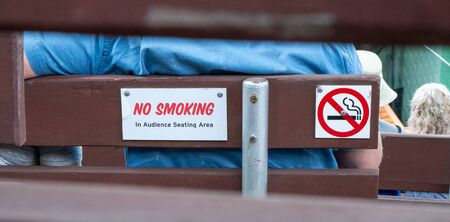 Closeup of a NO SMOKING sign on the back of a wooden bench at an outdoor concert venue.