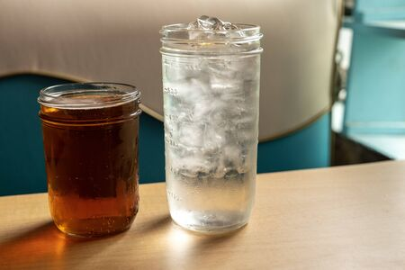 Two cold beverages with condensation on glass sitting on a table in a retro cafe with natural light. Cold refreshing drink to quench your thirst.