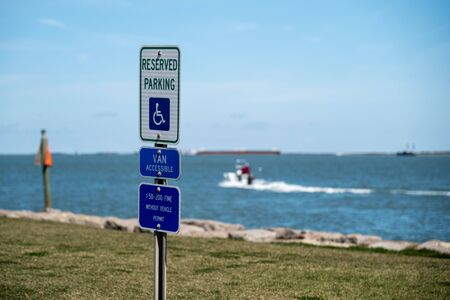 Handicapped parking sign near water with out of focus boat leaving shore in background, on a sunny day in Port Aransas, Texas.