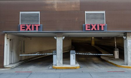 Two Parking Garage Ramp Exits with Red Exit Signs over doorways where cars leave the building.