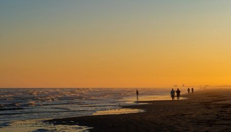 Tranquil beach scene at sunset with waves, clear sky and silhouette of a few unidentifiable people.