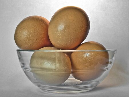 Brown eggs in transparent bowl with drops of moisture from condensation.