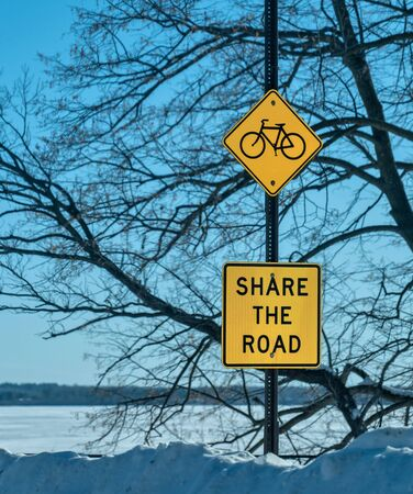 SHARE THE ROAD bicycle sign posted in a park, with tree branches, blue sky and a snow covered lake in the background, on a sunny, picturesque winter day.