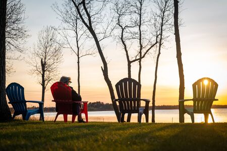 A person sitting in one of four adirondack chairs, overlooking the lake at sunset on a clear day. Silhouette of chairs and trees.