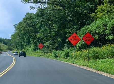 Orange signs warning of UNEVEN LANES, LOW SHOULDER and BUMP along a curvy asphalt highway with cars on road and trees and wild flowers on the side. Stock fotó
