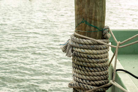 Nautical rope tied to a wood pole on a boat dock, with water in the background.