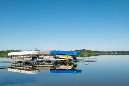 Docked boats on lifts are reflected in the calm water of a pretty lake in Minnesota, on a sunny summer day with beautiful clear blue sky. Фото со стока