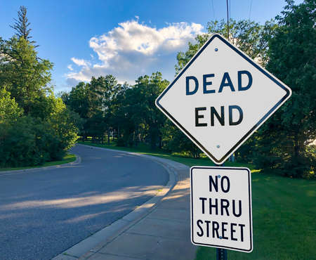 White Warning Road Signs on DEAD END street and NO THRU STREET along road and sidewalk in evening.