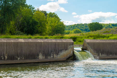 Water flows through the floodgate in a concrete dam on a river, with green trees and vegetation on the hills in the background. Фото со стока