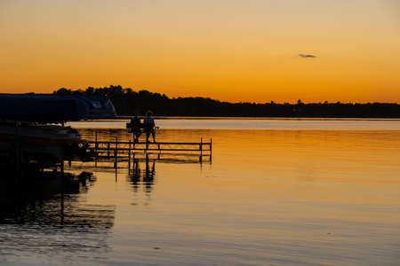 Evening scene at a lake in Bemidji, Minnesota, with silhouette of two people sitting on a dock bench, and a few ripples on the reflective water.