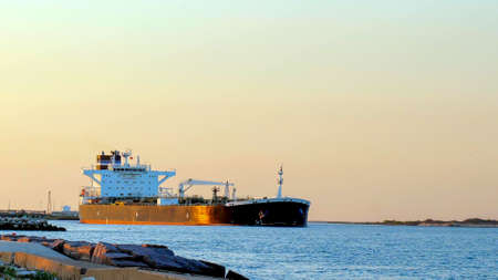 A Crude Oil Tanker Ship, on the shipping channel between the Gulf of Mexico and Corpus Christi, Texas, sails past Port Aransas on a clear sunny evening. Фото со стока