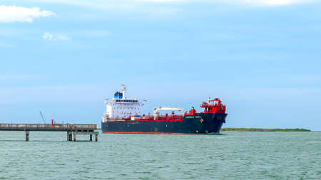 PORT ARANSAS, TX - 24 FEB 2020: The OVERSEAS TAMPA, an oil chemical tanker, sails past a pier on the ship channel between Corpus Christi, Texas and the Gulf of Mexico. Редакционное