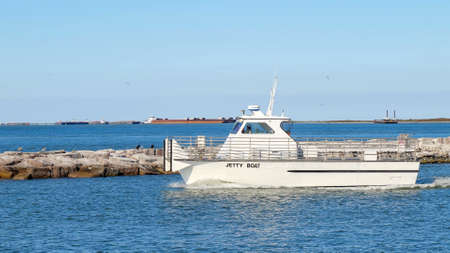 PORT ARANSAS, TX - 27 FEB 2020: Jetty boat leaves the marina entrance on a sunny day as it goes to retrieve passengers from San Jose Island.