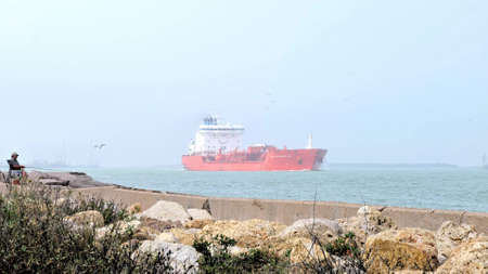 PORT ARANSAS, TX - 10 FEB 2020: Fisherman on the jetty as a crude oil tanker ship, the ALESSANDRO DP, sails on the shipping channel between Corpus Christi and the Gulf of Mexico on a foggy day.