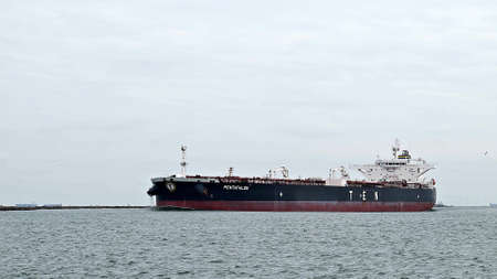 PORT ARANSAS, TX - 31 JAN 2020: The PENTATHLON, an oil tanker ship sails past the South Jetty on the water of the shipping channel between the Gulf of Mexico and a Corpus Christi, Texas refinery. Редакционное
