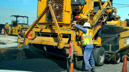 PORT ARANSAS, TX - 28 FEB 2020: Road construction machine laying new asphalt on city street. Working man in hardhat and yellow machine and fresh black asphalt tar, on a sunny day.