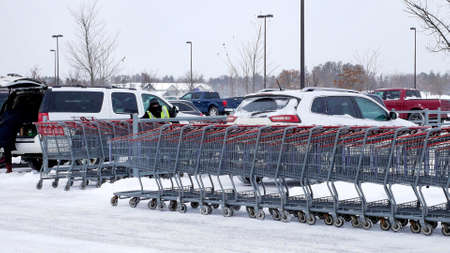 A row of grocery shopping carts on a winter day in a snow covered parking lot with many vehicles. Фото со стока