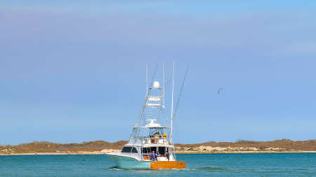 PORT ARANSAS, TX - 28 FEB 2020: The FREEBIRD, a beautiful fishing yacht boat sails on the calm blue water on a sunny day.