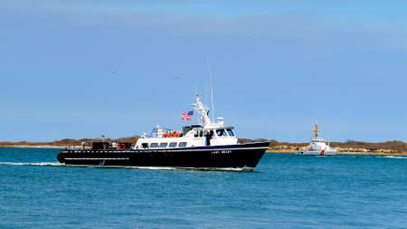 PORT ARANSAS, TX - 28 FEB 2020: The LADY BECKY, a commercial boat boat sails on the calm blue water on a sunny day, with a Coast Guard cutter in the distance.