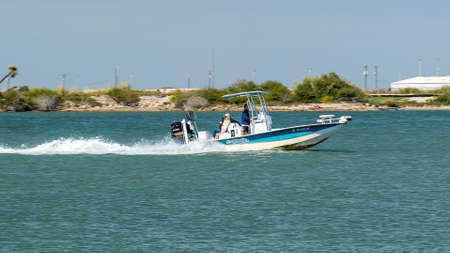 PORT ARANSAS, TX - 28 FEB 2020: Fast moving fishing boat with outboard motor on the water, on a sunny day in Texas.