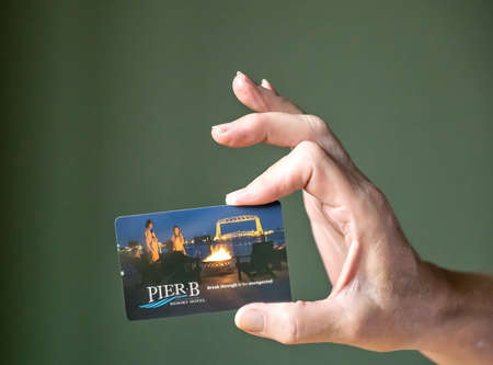 BEMIDJI, MN - 20 JUL 2020: Womans hand holding room security keycard for Pier B Resort in Duluth, Minnesota, in close-up view.