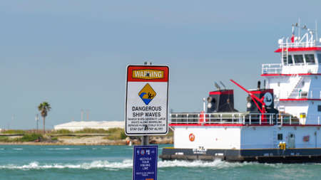 PORT ARANSAS, TX - 28 FEB 2020: Signs warning of DANGEROUS SHIP WAVES and a reminder to RECYCLE YOUR FISHING LINE, as a boat sails past. Редакционное