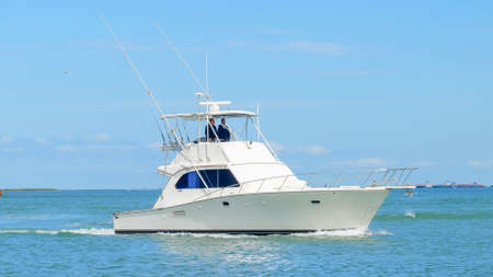 PORT ARANSAS, TX - 29 FEB 2020: Angled view of a beautiful white fishing yacht boat sails on the calm blue water as it approaches the marina on a sunny day. Редакционное