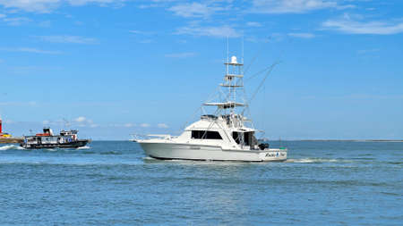 PORT ARANSAS, TX - 28 FEB 2020: Angled view of a beautiful white fishing yacht boat sails on the calm blue water as it leaves the marina on a sunny day.