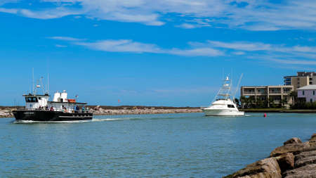 PORT ARANSAS, TX - 29 FEB 2020: A tour boat and a fishing yacht boat sail right to left, out of the marina, on the calm blue water on a sunny day.