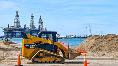 PORT ARANSAS, TX - 29 FEB 2020: Yellow CAT 289D front loader carries a full bucket load of dirt at a construction site, across the water from three oil rigs in dry dock. Редакционное