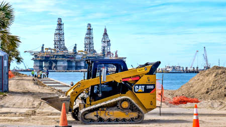 PORT ARANSAS, TX - 29 FEB 2020: Yellow CAT 289D front loader with an empty bucket, used to carry dirt at a construction site, across the water from three oil rigs in dry dock.