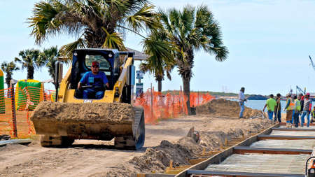 PORT ARANSAS, TX - 29 FEB 2020: Working man drives a yellow CAT 289D front loader to move a load of dirt at a construction site near the water. Редакционное