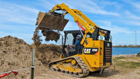 PORT ARANSAS, TX - 29 FEB 2020: Working man drives a yellow CAT 289D front loader machine to empty a load of dirt at a construction site near the water. Редакционное