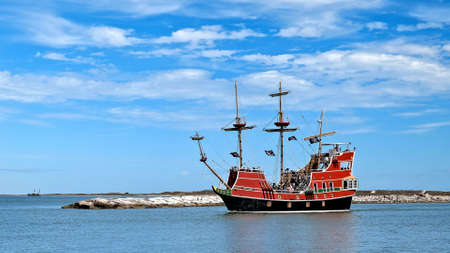 PORT ARANSAS, TX - 29 FEB 2020: The Red Dragon Pirate Cruise, a tourist excursion boat with passengers and entertaining crew, leaves the marina.