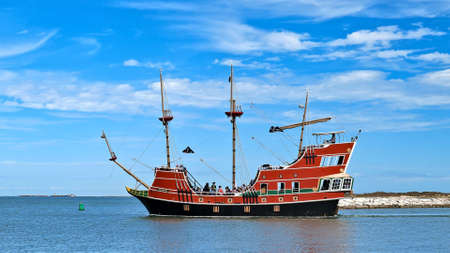 PORT ARANSAS, TX - 29 FEB 2020: Broadside view of the Red Dragon Pirate Cruise, a tourist excursion boat with passengers and entertaining crew, leaves the marina. Редакционное