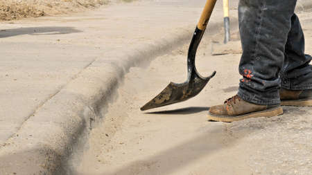 Construction workers use a shovel to clean dirt off the street next to the sidewalk at a work site. Closeup of boots, shovel, dirt and curb.