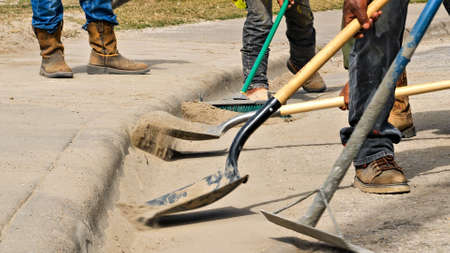 Construction workers use shovels and broom to clean dirt off the street by the sidewalk at a work site. Closeup of boots, shovels, dirt, and curb. Фото со стока