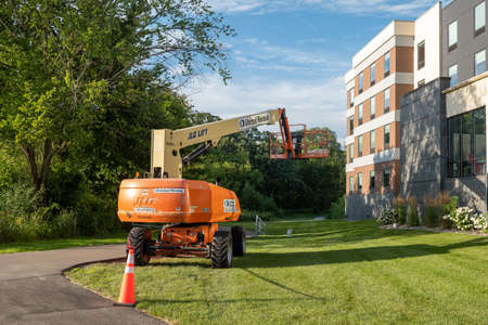ROCHESTER, MN - 29 JUL 2020: JLG Articulating Boom Lift standing by the side of the building. Редакционное