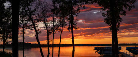 Sunset reflecting in the water of a beautiful lake with trees, dock, lifts, and a boat in the foreground in silhouette.