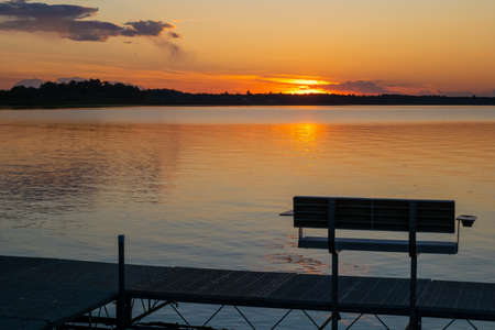 Evening scene at a lake in Bemidji, Minnesota, with an empty dock bench, and a few ripples on the reflective water.